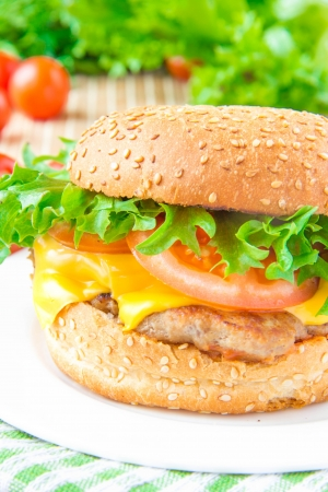Tasty american lunch - cheeseburger with meat rissoles, cheddar cheese, lettuce and tomato photo