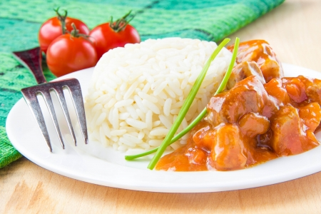 Chinese dish is pork in sweet and sour sauce with white rice on plate photo