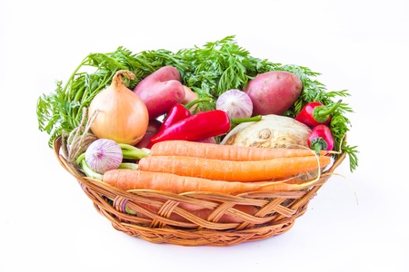 Assortment of fresh young vegetables in a basket on white photo