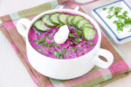 polish lithuanian: Traditional cold Lithuanian summery soup made of beets, cucumbers, egg and herbs in white plate