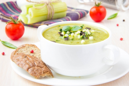 Vegetable green healthy cream soup with avocado, celery, zucchini and herbs in a white cup as an appetizer photo