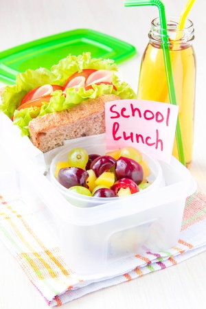bento: Bento lunch for your child in school, box with a healthy sandwich and fruit salad and apple juice in the bottle for drinking Stock Photo