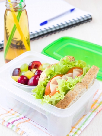 plastic box: Bento lunch for your child in school, box with a healthy sandwich and fruit salad and apple juice in the bottle for drinking Stock Photo