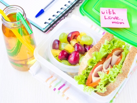 bento box: Bento lunch for your child in school, box with a healthy sandwich and fruit salad and apple juice in the bottle for drinking Stock Photo