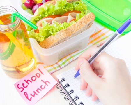 Bento lunch for your child in school, box with a healthy sandwich and fruit salad and apple juice in the bottle for drinking photo