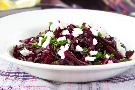 Delicious healthy beet salad with feta cheese, parsley and olive oil photo