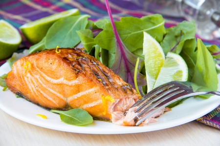 Grilled fillet of red salmon and salad with green leaves of lettuce and spinach, tasty food photo