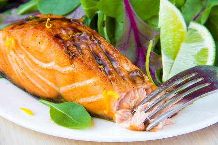 Grilled fillet of red salmon and salad with green leaves of lettuce and spinach, tasty dish