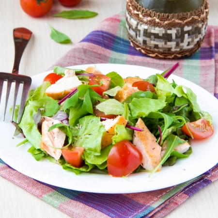 Delicious fresh salad with salmon, lettuce, cherry tomatoes and herbs, restaurant appetizer