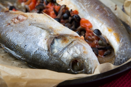 Baked whole white fish, sea bass stuffed with black olives, capers and tomatoes, homemade dinner photo