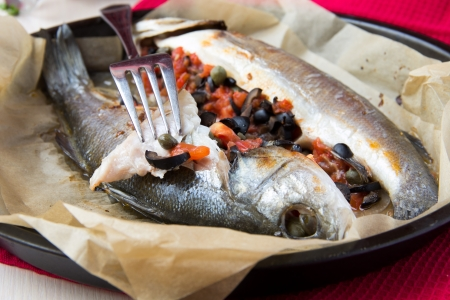 Grilled whole white fish, sea bass stuffed with black olives, capers and tomatoes, tasty dish photo
