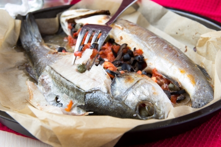 Baked whole white fish, sea bass stuffed with black olives, capers and tomatoes, macro photo