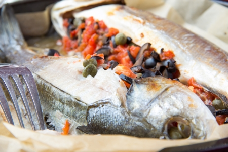 Baked whole white fish, sea bass stuffed with black olives, capers and tomatoes, close up photo