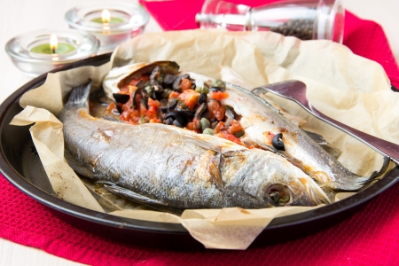 Baked whole white fish, sea bass stuffed with black olives, capers and tomatoes photo