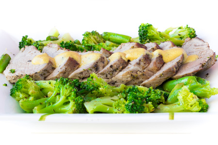 leguminous: Baked, sliced fillet of pork with green vegetables, broccoli and leguminous haricot, isolated on white background
