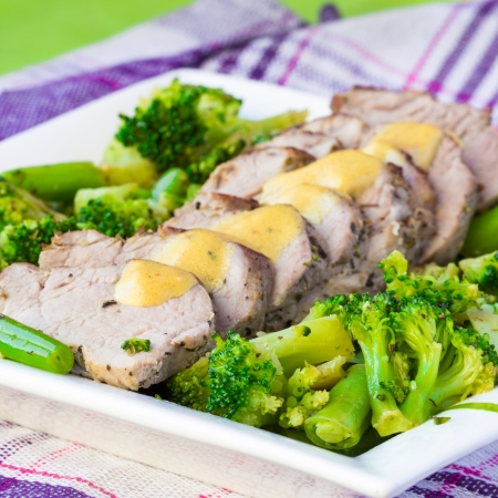 leguminous: Baked, sliced fillet of pork with green vegetables, broccoli and leguminous haricot, isolated on white background, tasty dish for dinner