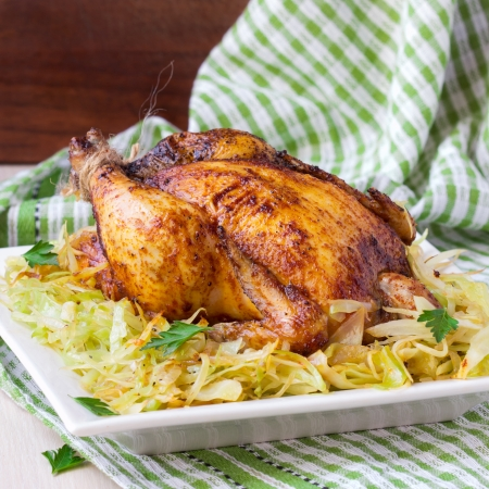 stewed: Roasted whole chicken with golden crust and garnish of stewed cabbage, tasty dinner