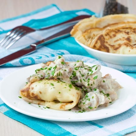 pancake week: Russian pancakes with chicken and mushrooms champignon with white sauce, shrovetide