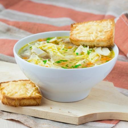 sopa de pollo: Sopa de pollo con fideos, zanahorias y picatostes de queso Foto de archivo