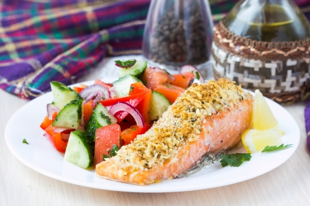Steak fillet of red fish salmon with cheese crust breading and fresh vegetable salad