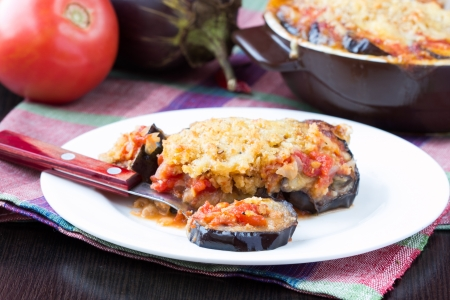 Tasty Italian dish, appetizer with eggplant, cheese and tomato sauce, portion on plate