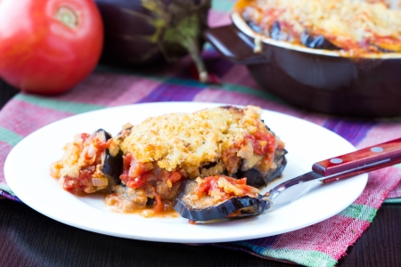Tasty Italian dish, appetizer with eggplant, cheese and tomato sauce, portion on plate photo