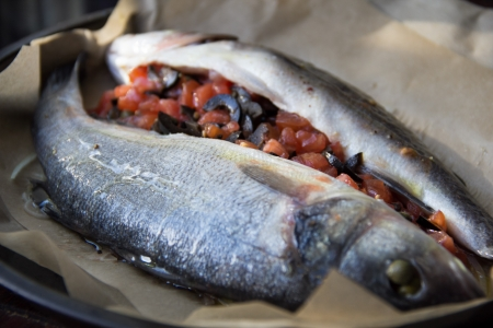 Cooking tasty fish, sea bass,stuffing is stuffed with olives, capers and tomatoes photo