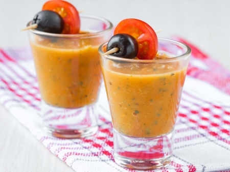 Vegetable soup in small glasses with olives, starter, tasty appetizer for guests photo