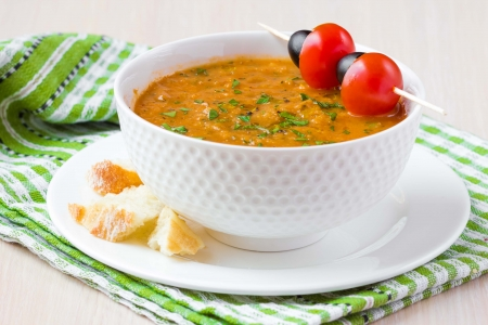 Vegetable soup in bowl with tomato and olive photo