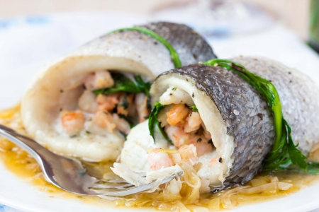 Fish rolls of dorado fillet stuffed shrimp and spinach with onion sauce of leek and wine photo