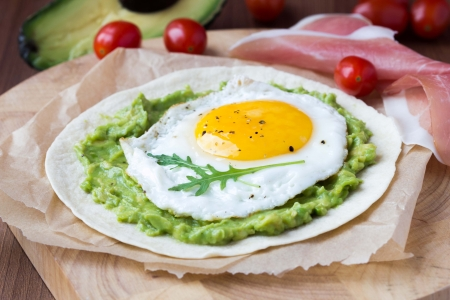 Breakfast with fried egg and sauce of avocado on grilled flour tortilla, Mexican dish huevos rancheros