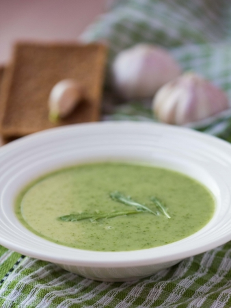 Green garlic cream soup with leaves rukola, arugula, healthy dietary vegetable dish photo