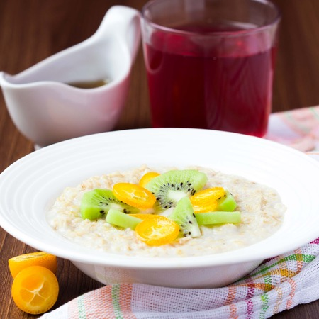 kasha: Oat porridge with fruit, orange, cumquat, kiwi, maple syrup, delicious, healthy breakfast