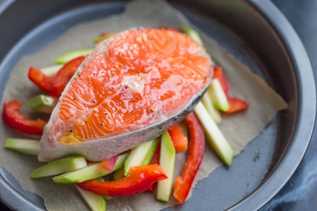 Cooking raw steak of red fish salmon on vegetables, zucchini, sweet pepper, tasty healthy dish photo