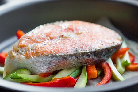 Cooking steak of red fish salmon on vegetables, zucchini, sweet pepper, delicious homemade dish photo