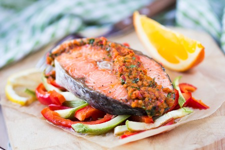 Steak red fish salmon on vegetables, zucchini and paprika with salsa, tasty diet dinner photo