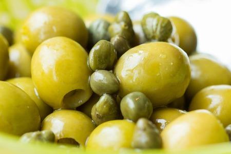 alcaparras: Aceitunas verdes y alcaparras en un taz�n, primer plano, ingredientes italianos, macro