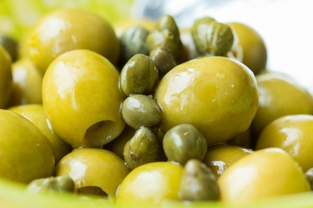 Green olives and capers in bowl, closeup, Italian ingredients, macro 版權商用圖片