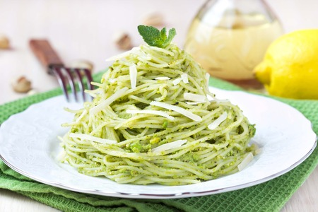Italian green pasta spaghetti with pesto green peas, mint, pistachios, parmesan cheese, delicious healthy vegetarian appetizer 版權商用圖片