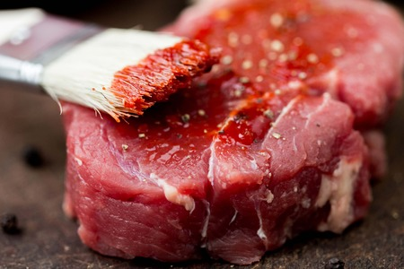 greased: Raw beef steak, greased tomato sauce brush, cooking delicious dinner