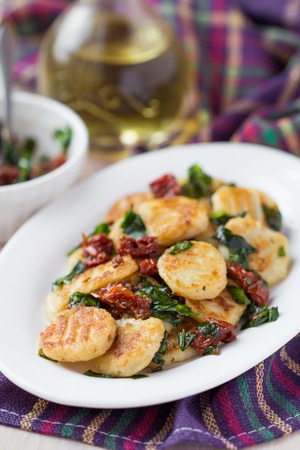 meagre: Fried potato gnocchi with sauce of dried tomatoes, spinach, Italian delicious homemade dish Stock Photo