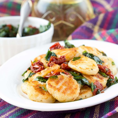 rubicund: Fried potato gnocchi with sauce of dried tomatoes, spinach, Italian delicious homemade dish Stock Photo