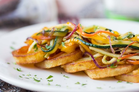 meagre: Fried slices of potato with finely chopped sticks vegetables, lean, vegetarian dish for dinner