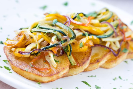 Fried slices of potato with finely chopped sticks vegetables, lean, vegetarian dish for dinner
