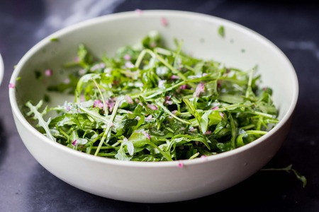 Fresh green salad with arugula, onion sauce, olive oil photo