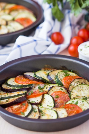 Ratatouille, vegetables cut into slices, eggplant, zucchini, tomatoes baked in oven photo