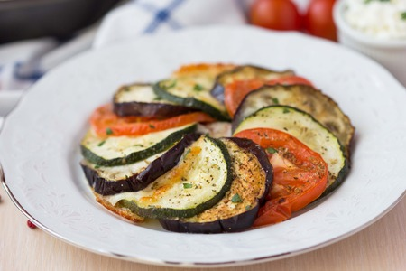 Ratatouille, vegetables cut into slices, eggplant, zucchini, tomatoes on plate, delicious vegetarian dish photo