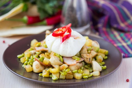 Hot appetizer salad with potatoes, ham, green peas, mushrooms, poached egg with resultant yolk photo