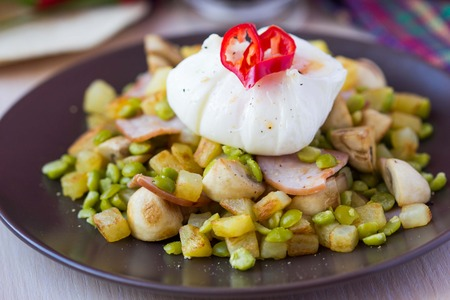 papas doradas: Ensalada de aperitivo caliente con patatas, jamón, guisantes, champiñones, huevo escalfado con yema resultante