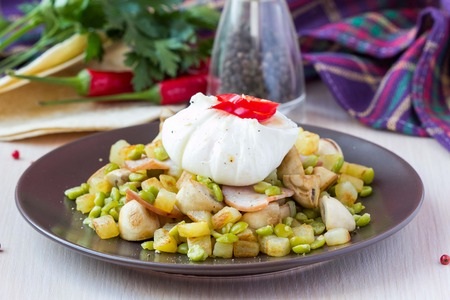 Hot appetizer salad with potatoes, ham, green peas, mushrooms, poached egg, tasty dish photo